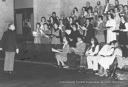 Années 1970 : le père Martial Caron dirige la Chorale des Intrépides dans la salle Pauline-Boutal du CCFM. En médaillon : le père Martial Caron, s.j.