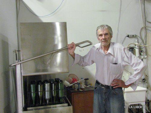 Armand Bédard, posant ici dans sa boutique Moonshiners Unlimited auprès d'une machine qui sert à laver et stériliser les bouteilles.