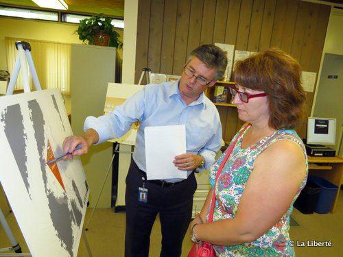 Le gérant des services bibliothécaires de la Ville de Winnipeg, Rick Walker, souligne un des éléments d'un dessin architectural de la future nouvelle bibliothèque du Parc Windsor à une résidente de Southdale, Cheryl Bennet