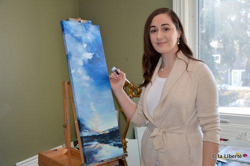 Emilie Lemay dans son atelier, au travail sur une peinture panoramique. « Dans la peinture, j'ai la liberté de mettre en avant ce qui me plaît. »