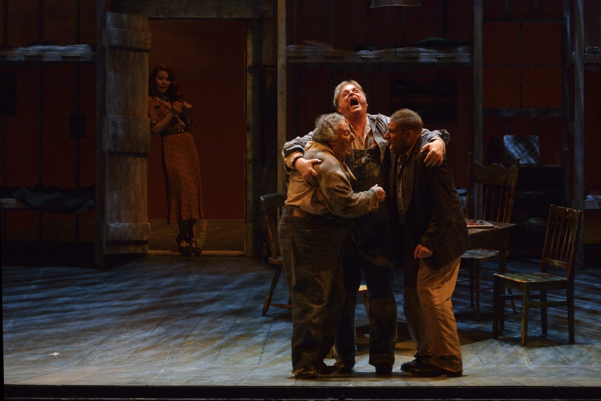 "Candy (Peter Strummer, left) and Lennie (Michael Robert Hendrick) and George (Gregory Dahl) celebrate that they can buy a farm as their future downfall, Curley's wife (Nikki Einfeld) watches from the doorway during Manitoba Opera's presentation of ""Of Mice and Men"". The opera, created by the American composer Carlisle Floyd and based on the John Steinbeck novella runs April 23, 26 and 29 at the Centennial Concert Hall in Winnipeg."